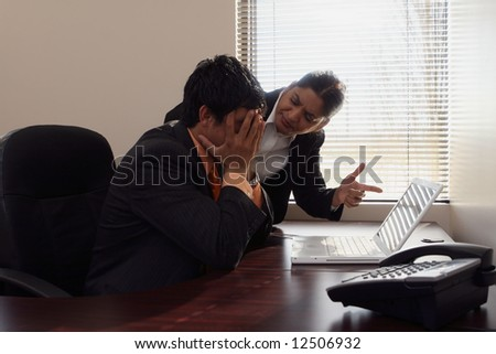 Female boss dressing down a younger male subordinate while pointing a finger at his laptop screen - stock photo