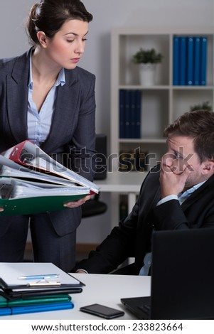 Female boss giving lot of work to her busy worker - stock photo