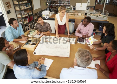 Female Boss Leading Meeting Of Architects Sitting At Table - stock photo