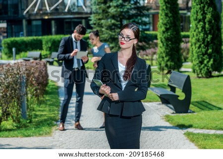 Female boss. Portrait of confident business people outside the office. On background are businessmen