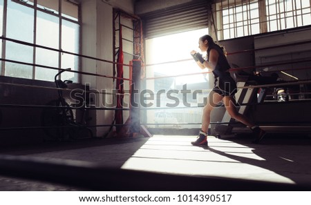 Female boxer doing shadow boxing inside a boxing ring. Boxer practicing boxing moves at a boxing studio.