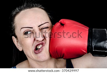 Female boxer getting hit in the face by boxing glove. Black background.