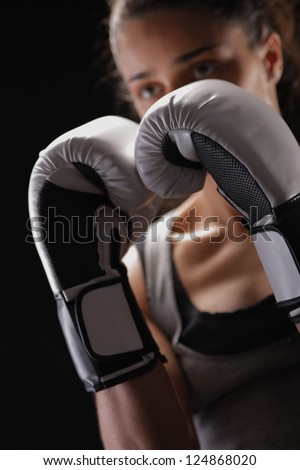 Female boxer is fighting, focus on boxing glove - stock photo