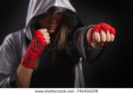 Female boxer makes a fight with a shadow, silver boxing robe and red boxing wraps, black background. Strong and confident, she will be a champion.