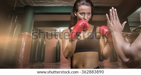 Female boxer with fighting stance against trainer hand against red boxing area with punching bags - stock photo