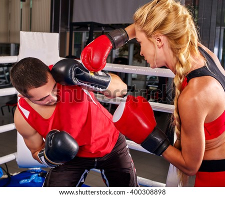 Female boxer with your male coach on workout in gym. Girl shoots  man in ear.
