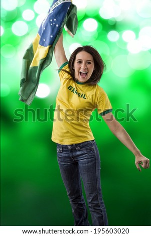 Female brazilian fan celebrating on a green lights background.
