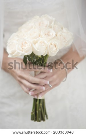 Female bride hold a bouquet of roses