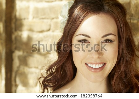 Female bride standing against sunny wall smiling