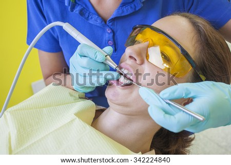 Female brown haired patient in medical glasses having dental check up in a dentist room female from dentist wearing mask and light blue gloves