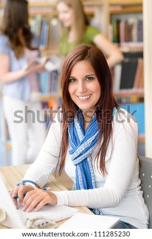 Female brunette student at high school library working on laptop - stock photo