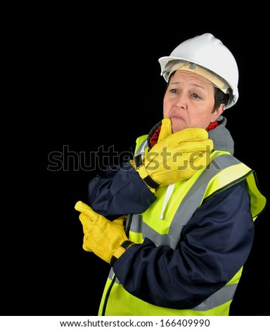 female builder/construction worker standing thinking. Isolated image on black background. - stock photo