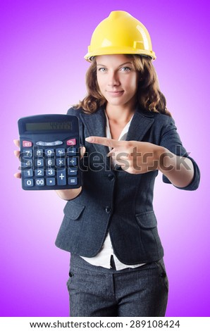 Female builder with calculator against the gradient