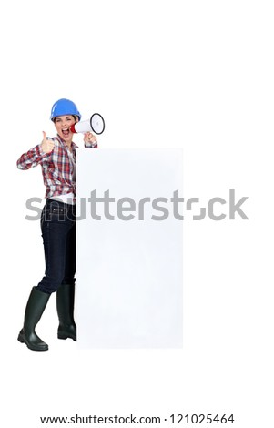 Female builder with megaphone and advertising board - stock photo