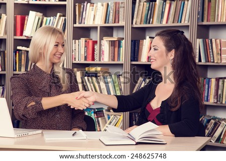 Female business. Conversation women office. Two young businesswomen having a meeting in the office sitting at a desk having a discussion. Two girls students discuss  material. Work on the computer. - stock photo