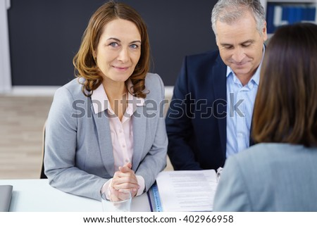 Female business executive in a meeting with a male and female colleague sitting together at a table in the office looking up at the camera with a quiet smile - stock photo