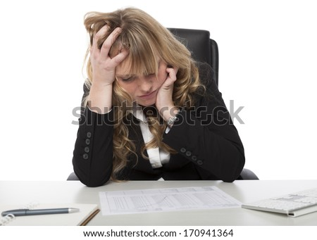 Female business executive studying a report at her desk rumpling her hair with her hand as she concentrates on the contents - stock photo