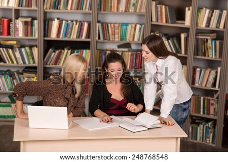 Female business. Female staff met to discuss the new information. A group of girls students in the library to discuss the news. Women came together to talk about the business case. Meeting friends. - stock photo