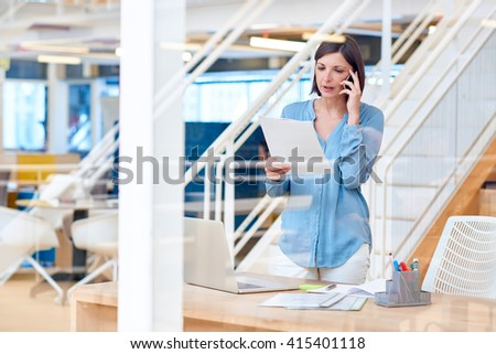 Female business manager reading report while talking on her phon - stock photo