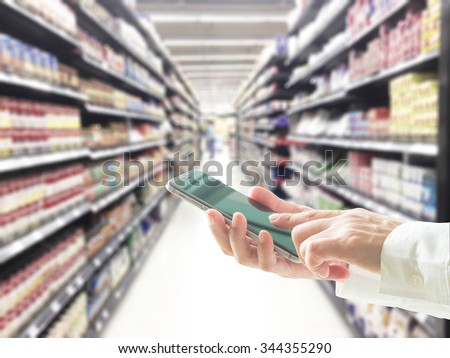 Female business person hand using cellphone on blur abstract background supermarket: Woman typing on touchscreen shopping on mobile phone: Internet ordering buying telecommunication payment ppc im seo - stock photo