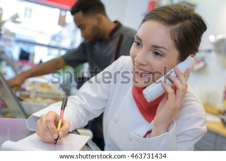 female butcher on the phone behind counter