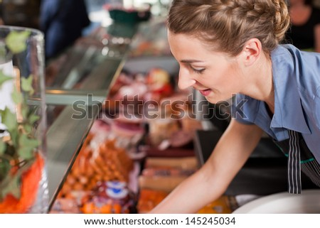 Female butcher picking fresh food for selling at butchery