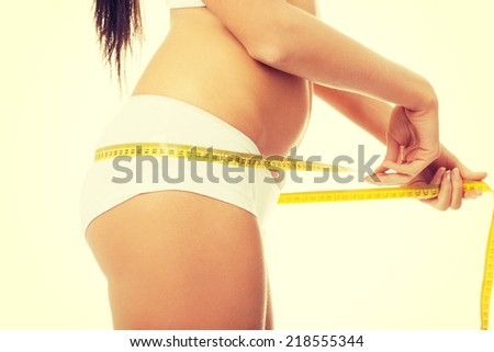 Female buttocks with a measurement tape. Isolated on white