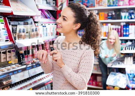 Female buying CC cream in makeup section - stock photo