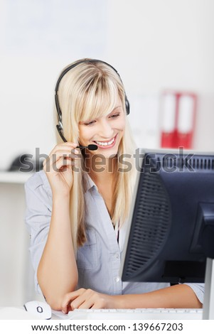 Female call center agent smiling while browsing in her computer
