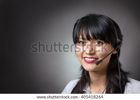 female call center assistant or telemarketer wearing a headset looking at the camera with a charming friendly smile, shot on a grey background. - stock photo