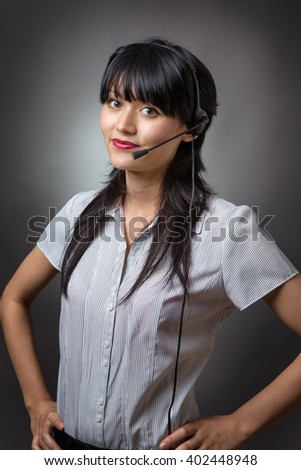 female call center operator, client services assistant or telemarketer wearing a headset looking at the camera with a charming friendly smile - stock photo