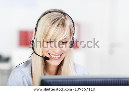 Female call center operator with headphone browsing on her computer - stock photo