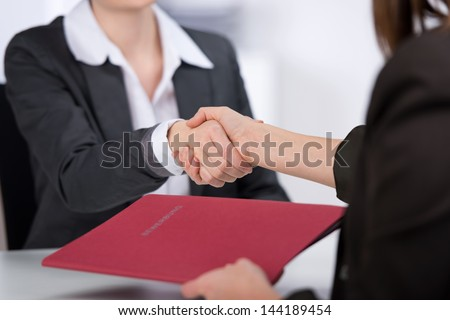 Female candidate shaking hands with businesswoman at desk in office