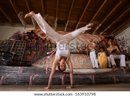 Female capoeira expert performing handstand splits - stock photo