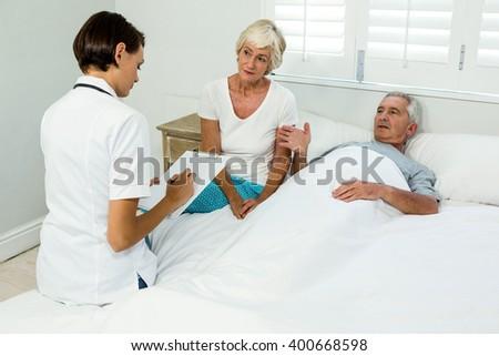 Female caregiver assisting senior man in bedroom at home - stock photo