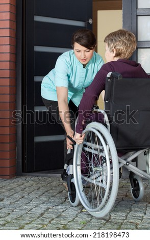 Female caregiver helping disabled woman on wheelchair entering home