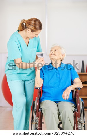 Female caregiver holding hand of an old woman in a wheelchair - stock photo
