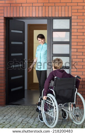 Female caregiver inviting elderly woman on wheelchair to nursing home