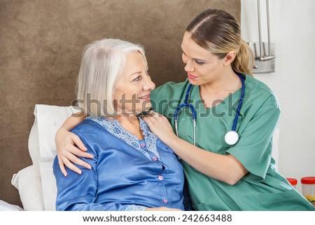 Female caretaker comforting senior woman in bedroom at nursing home - stock photo