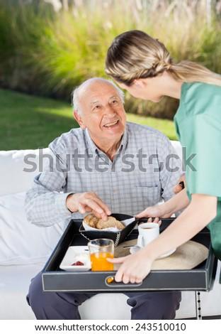 Female caretaker serving breakfast to senior man at nursing home - stock photo