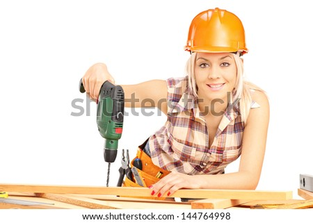 Female carpenter with helmet at work using hand drilling machine isolated on white background - stock photo