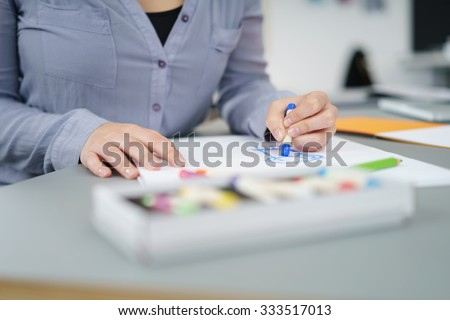 Female Cartoonist Draw Something on a White Paper Using Crayons at the Table Inside the Office.