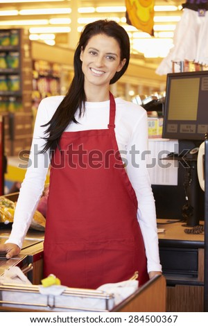Female Cashier At Supermarket Checkout