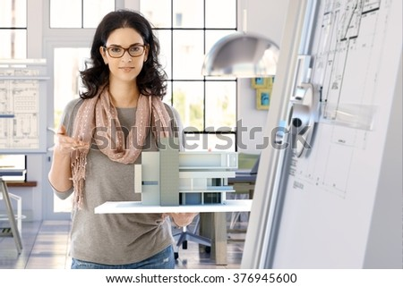 Female casual caucasian architect designer with building model holding in hand, standing, smiling, looking at camera. Bright office. - stock photo