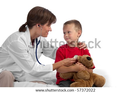 Female caucasian doctor giving a cute blond boy a physical, listening to his heart while he is hugging his bear - stock photo