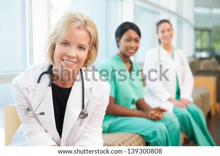 Female caucasian doctor sitting on couch with African-American nurse and hispanic nurse in hospital waiting area or lobby - stock photo