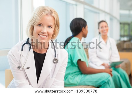 Female Caucasian doctor sitting on couch with African-American nurse and Hispanic nurse talking in background, in hospital waiting area or lobby