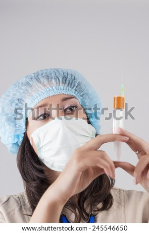 Female Caucasian Doctor with a Syringe and Endoscope Examining Vaccine for Test. Over Gray Background. Vertical Image - stock photo