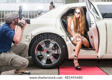 Female Celebrity Posing In Limousine For Paparazzi On Red Carpet