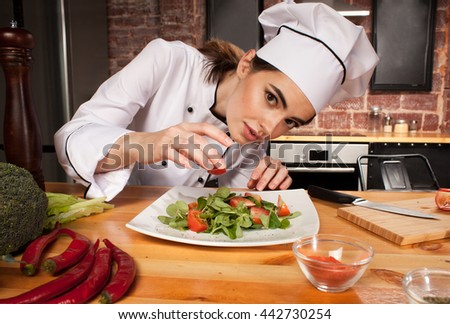Female chef cook preparing fresh salad with tomatoes on wooden table with pepper, broccoli, spices, tomatoes, salad and pepper mill - stock photo